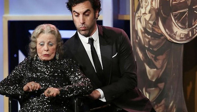 imagen Sacha Baron Cohen empuja a una viejita en silla de ruedas del escenario mientras recoge un premio (VIDEO)